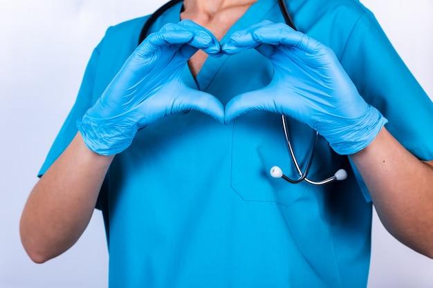 Docteur mains dans des gants en forme de coeur