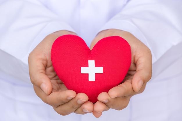 Docteur mains tenant un coeur rouge avec signe de donateur. concept de soins de santé.