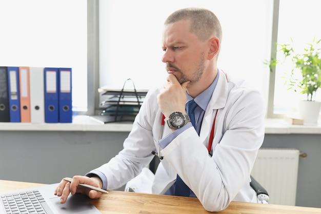 Docteur masculin regardant l'écran d'ordinateur portable dans le bureau