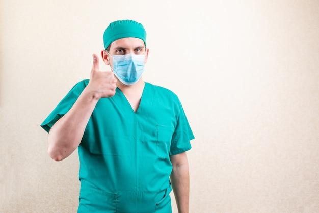 Docteur en masque et casquette, montrant les pouces vers le haut. photo de haute qualité