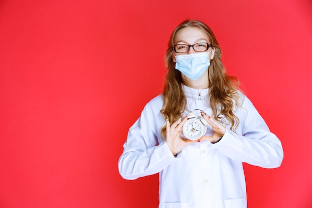 Docteur en masque facial montrant une horloge indiquant l'heure de prendre des médicaments.