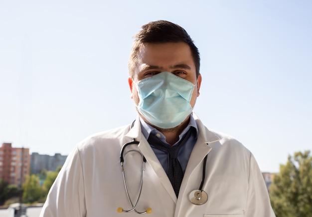 Docteur en masque médical à l'extérieur. traitement pendant la pandémie de coronavirus.