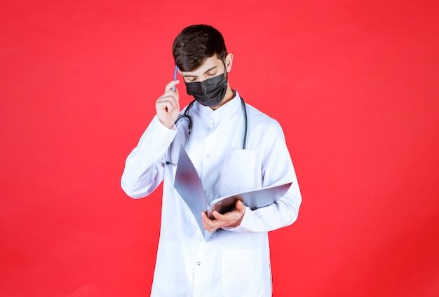 Docteur en masque noir pensant et prenant des notes sur un dossier noir.