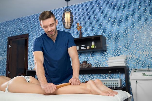 Docteur massant les jambes d'une cliente avec des bâtons de bambou