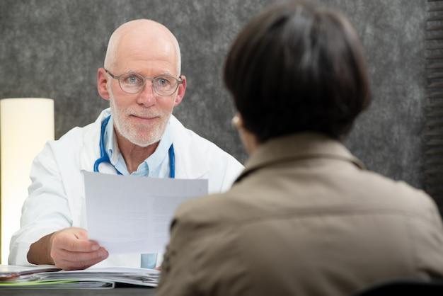 Docteur mature avec un patient au bureau