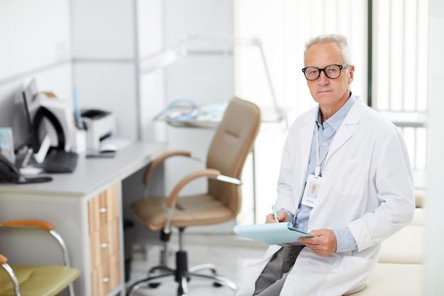 Docteur mature posant au bureau