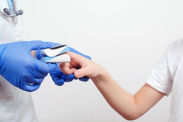 Le docteur mesure le pouls du patient et la saturation en oxygène du jeune garçon