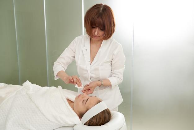 Le docteur met des aiguilles dans le visage féminin sur la thérapie de traitement d'acuponcture dans l'alternative de salon de station thermale