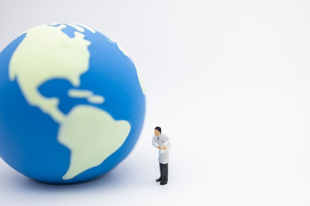 Docteur miniature figure debout et montre le presse-papiers avec mini balle du monde