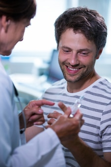 Docteur montrant l'injection pour le patient