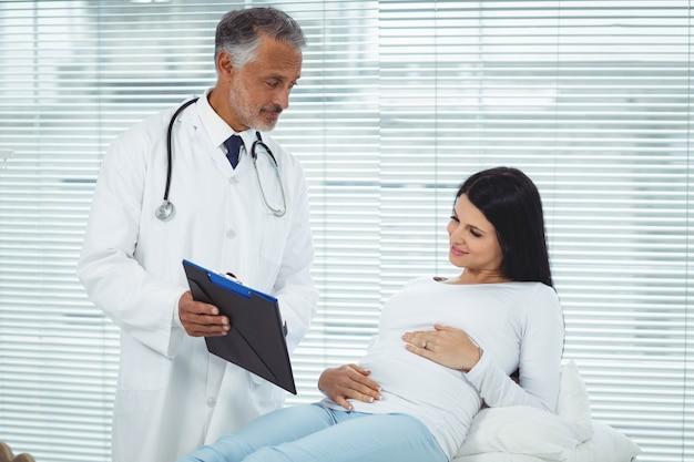 Docteur montrant des rapports à la femme enceinte dans la clinique