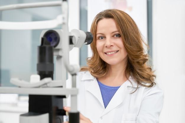 Docteur optométriste en blouse blanche posant avec lampe à fente.