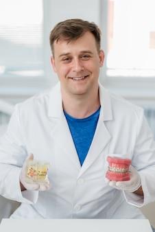 Docteur orthodontiste montre comment le système d'accolades sur les dents est organisé