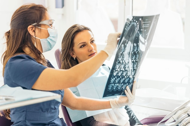 Docteur parlant avec son patient et enseignant une radiographie. notion de dentiste.