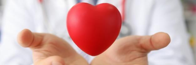 Docteur partageant un coeur rouge avec une croix dessus