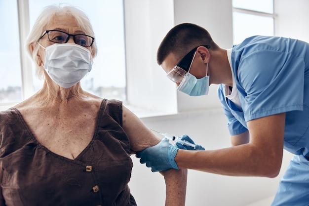 Docteur avec un passeport de vaccin de seringue dans des masques médicaux