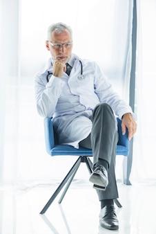 Docteur pensif assis sur une chaise