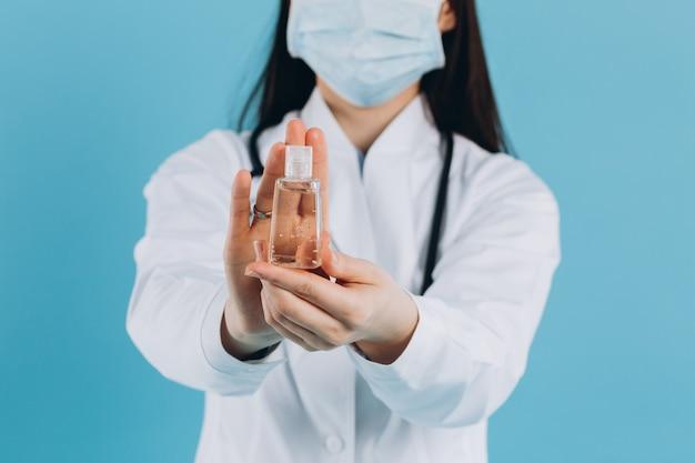 Docteur portant un masque facial chirurgical tenant montrant une bouteille de pompe de gel d'alcool. se laver les mains avec un gel d'alcool ou un savon désinfectant antibactérien. concept covid-19 ou coronavirus.