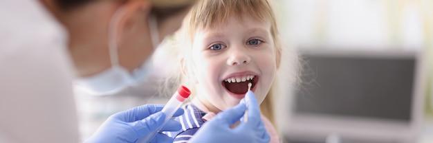 Le docteur prend une analyse de la petite fille avec le coton-tige