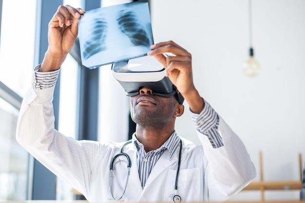 Docteur ravi levant les bras tout en tenant une photo aux rayons x