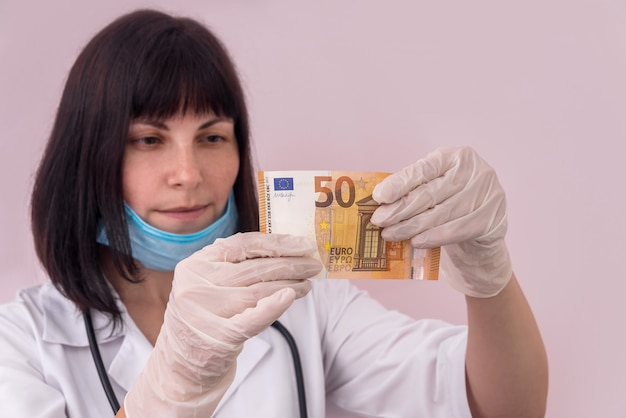 Docteur à la recherche de cinquante billets en euros le tenant dans des gants