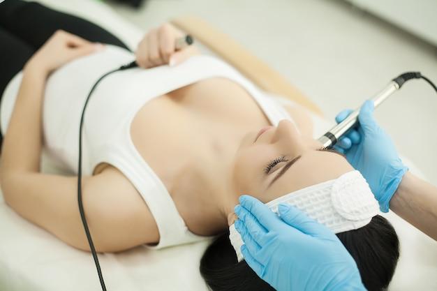 Docteur avec le scraber ultrasonique. faire la procédure de nettoyage par ultrasons du visage. modèle, profil. clinique cosmétologique. patient. soins de santé, clinique, cosmétologie.