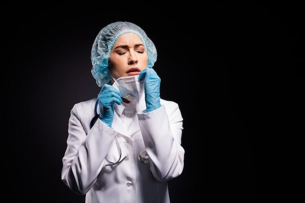 Docteur sérieux après le travail de nuit isolé sur fond de couleur noire