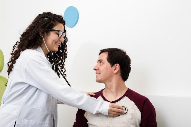 Docteur smiley vue de côté vérifiant un patient