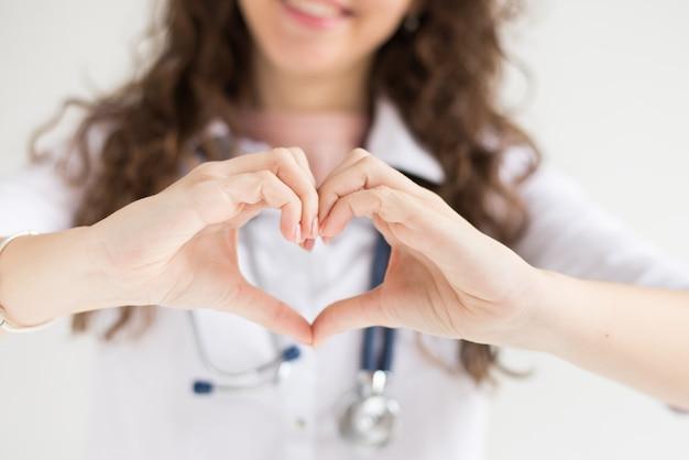 Un docteur avec son stéthoscope montre le cœur des mains
