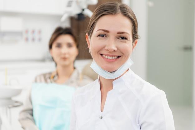 Docteur souriant à la caméra, avec son patient en attente d'être vérifié en arrière-plan