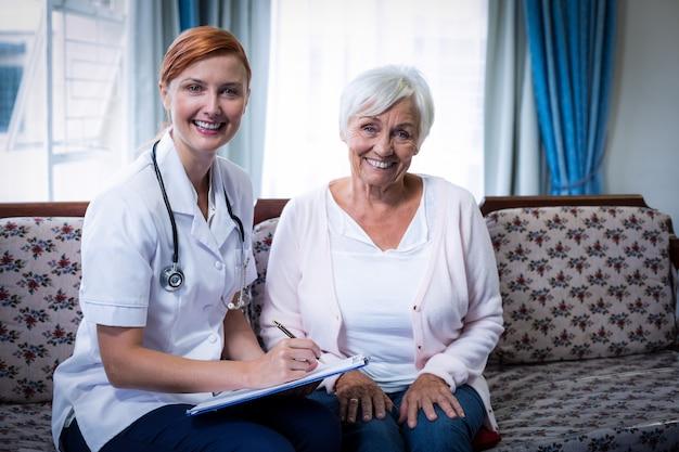 Docteur souriant, consultation, à, femme aînée
