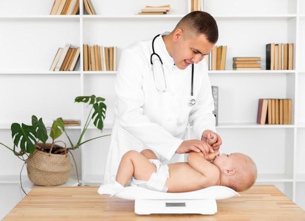 Docteur souriant pesant petit bébé