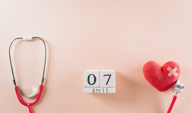 Docteur stéthoscope avec calendrier en bois et coeur rouge sur fond pastel