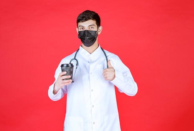 Docteur avec stéthoscope en masque noir tenant une tasse de café à emporter noire et appréciant le goût.