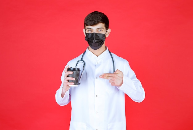 Docteur avec stéthoscope en masque noir tenant une tasse de café à emporter noire.