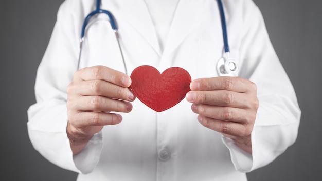 Docteur avec stéthoscope tenant coeur rouge.