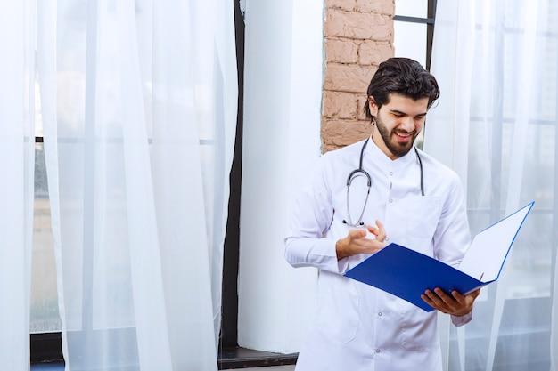 Docteur avec un stéthoscope tenant un dossier de rapport bleu et semble confus et réfléchi.