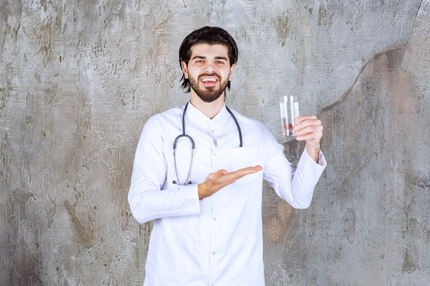 Docteur avec un stéthoscope tenant un verre d'eau pure et pointant quelque part