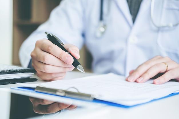 Docteur en tapant l'information travaillant dans le bureau de l'hôpital se concentrant sur le stéthoscope