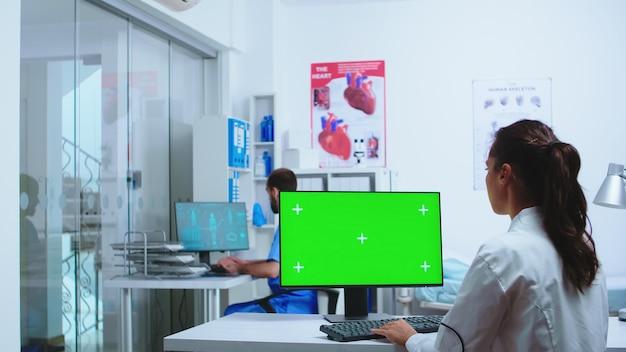 Docteur tapant sur ordinateur avec espace de copie à l'hôpital de médecine. infirmière travaillant avec un médecin spécialiste. ordinateur avec écran vert remplaçable utilisé par un spécialiste de la médecine à l'hôpital et portant