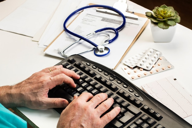 Docteur en tapant une prescription sur un ordinateur sur son bureau