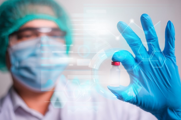 Docteur tenant une bouteille de vaccin avec un écran d'interface hud moderne sur fond d'hôpital, innovation et technologie médicale.