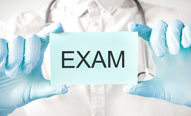 Docteur tenant la carte dans les mains et pointant le mot examen