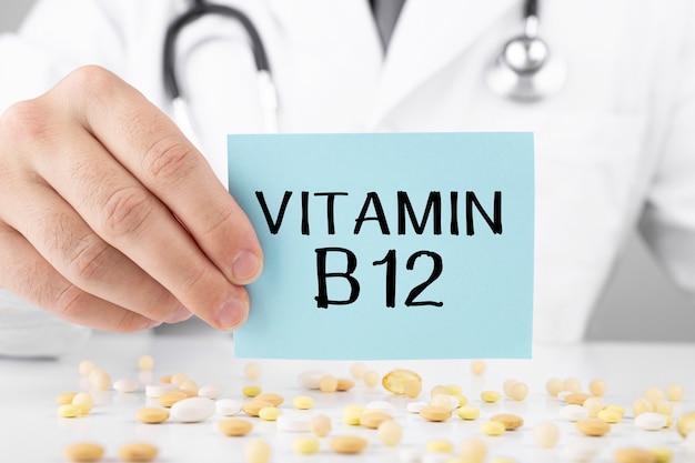 Docteur tenant une carte avec texte vitamine b12, concept médical