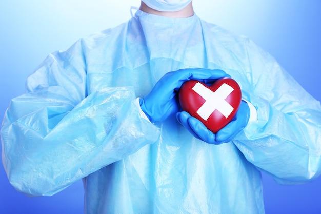 Docteur tenant le coeur décoratif sur le bleu