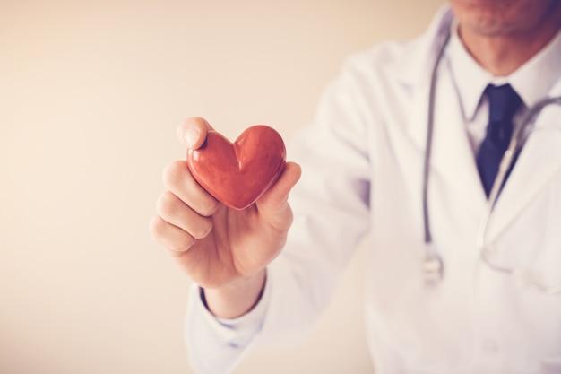 Docteur tenant coeur rouge, concept d'assurance maladie cardiaque