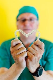 Docteur tenant deux aligneurs dentaires clairs en forme de coeur