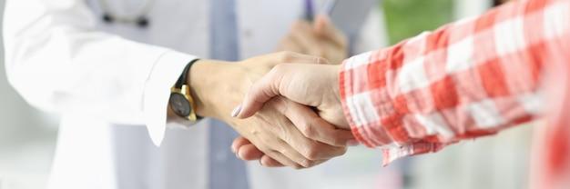 Docteur tenant des documents et serrant la main du patient dans la clinique en gros plan décharge du patient
