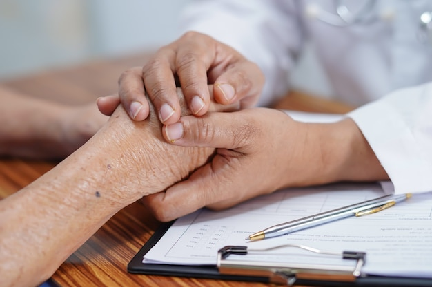 Docteur, tenant mains, à, asiatique, femme aînée, patient, à, love.