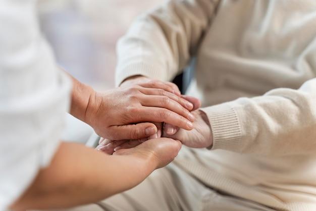 Docteur, tenant mains, à, patient senior